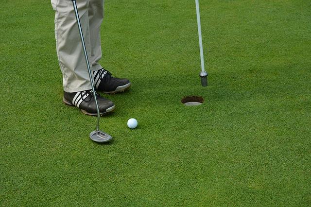 imagine cu jucator de golf aflat pe green langa cupa